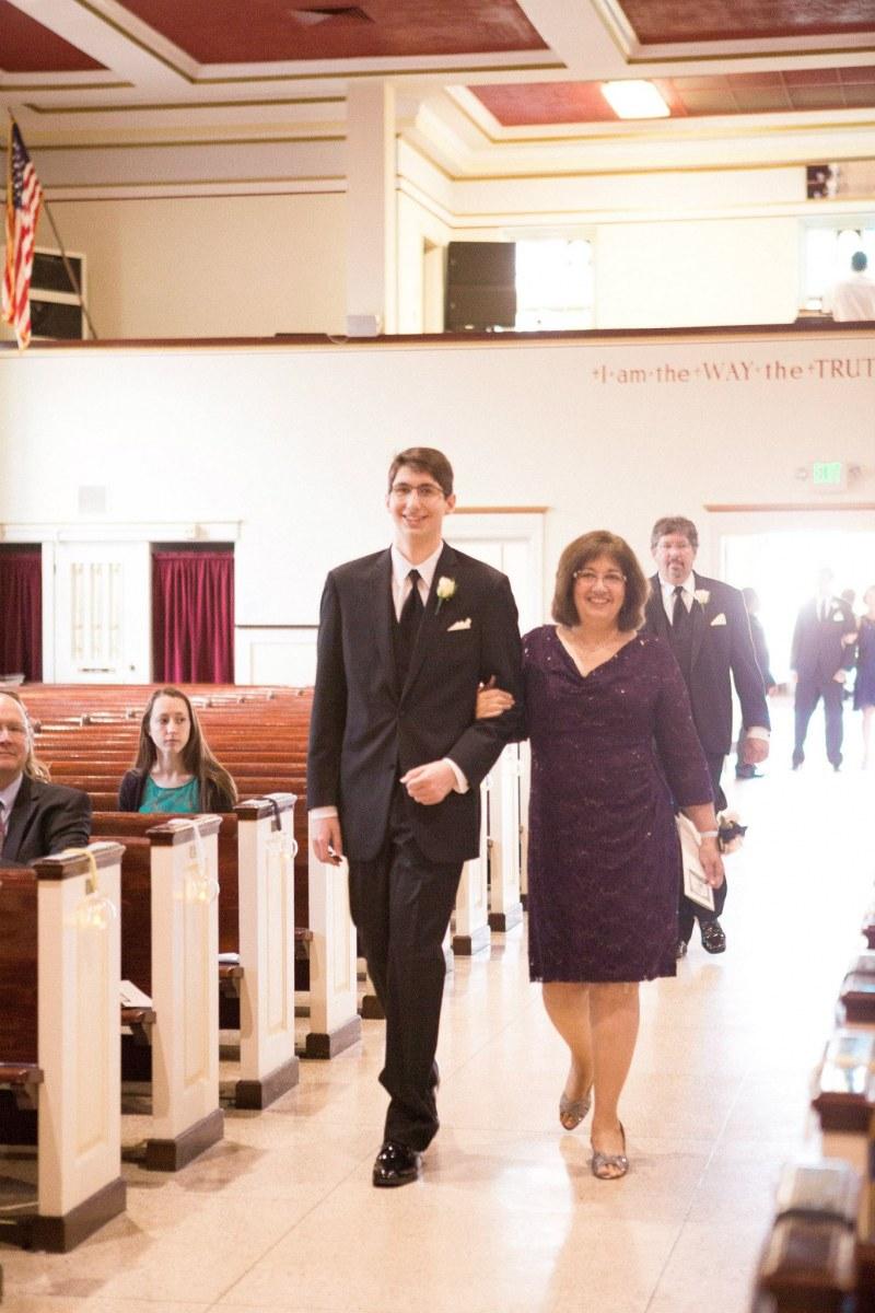 John escorts his mother at Gabe's wedding